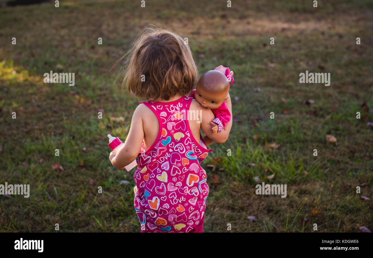 A toddler holds a baby doll and bottle - Stock Image