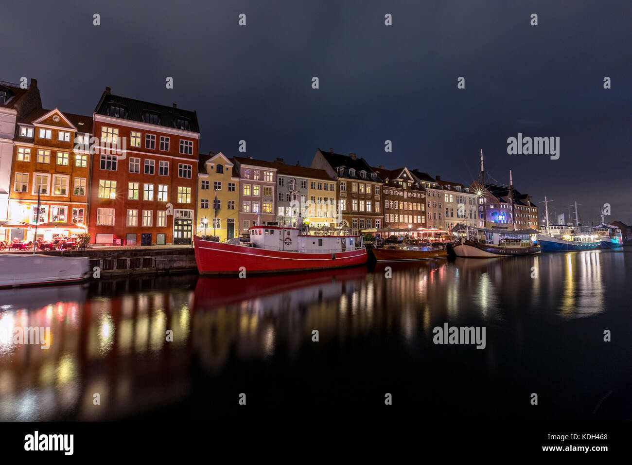 Scenic summer view of Nyhavn pier with color buildings, ships, yachts and other boats in the Old Town of Copenhagen, - Stock Image