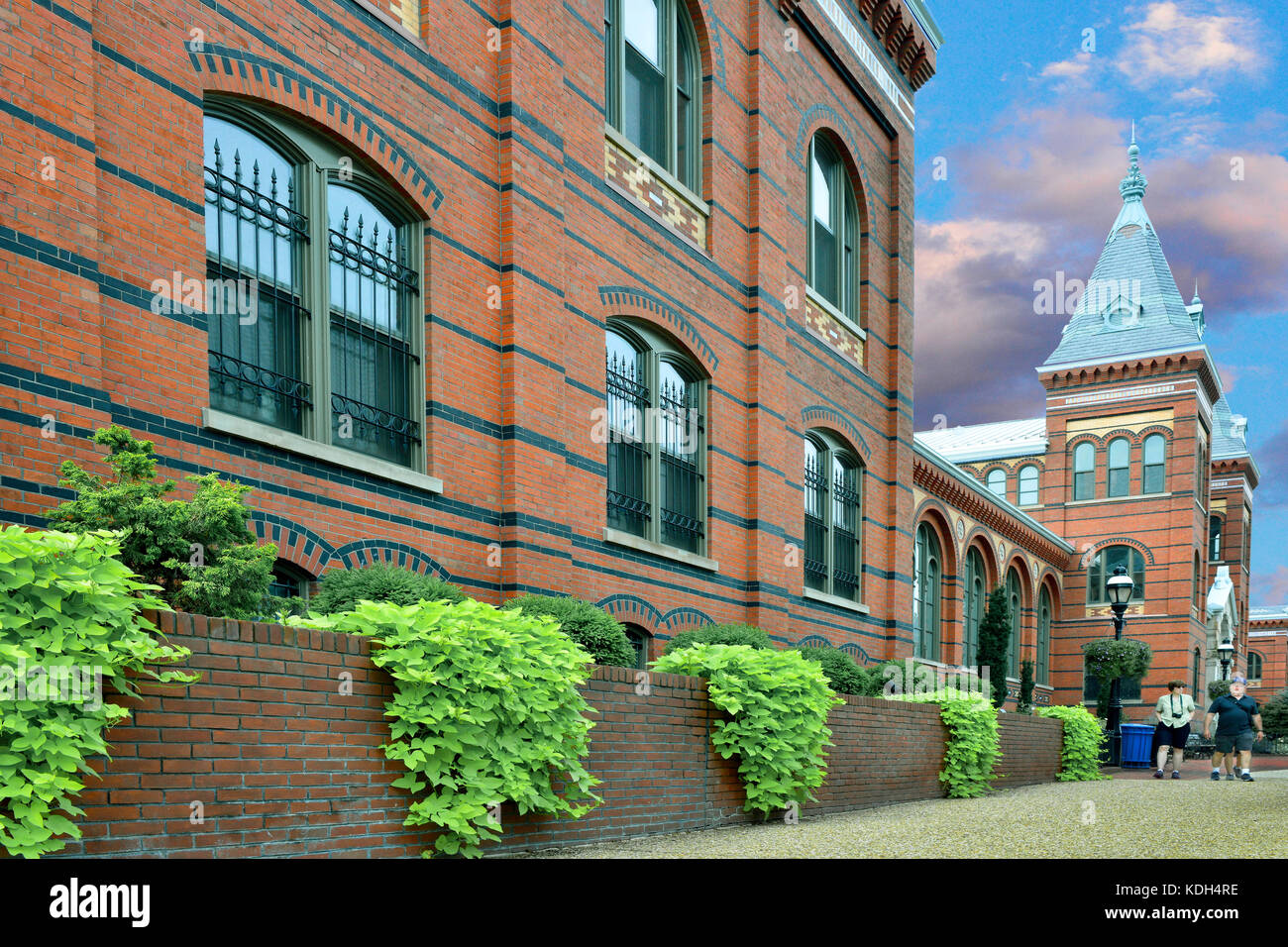 View along the sidewalk of a lovely landscaped wall around the red brick of the Smithsonian's Arts and Industries - Stock Image