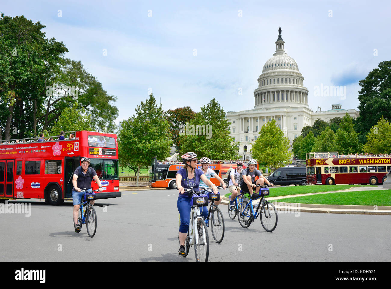 Bicycle tourists along with sightseeing buses circle in