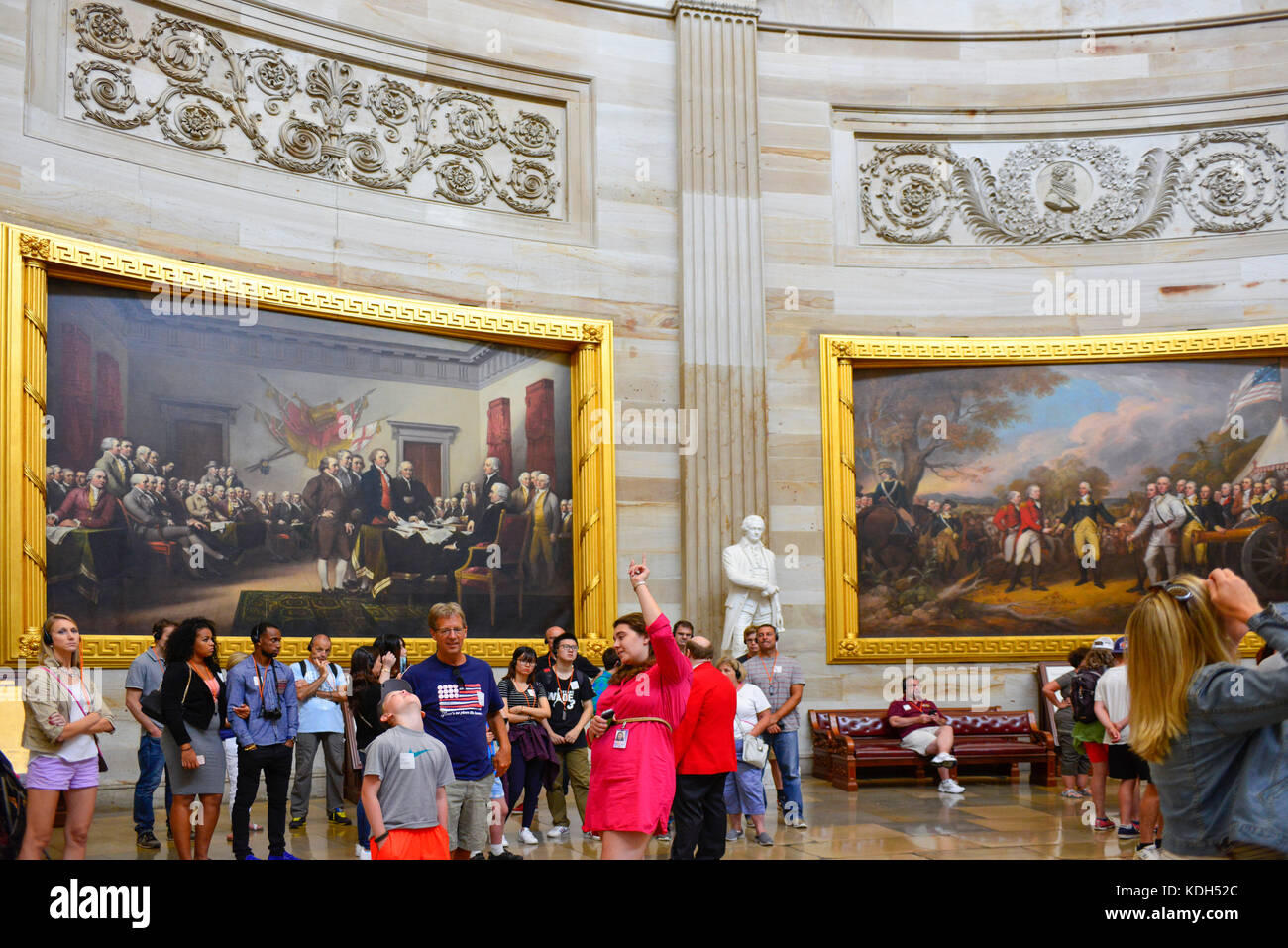 Female tour guide points to the famous paintings and murals inside.