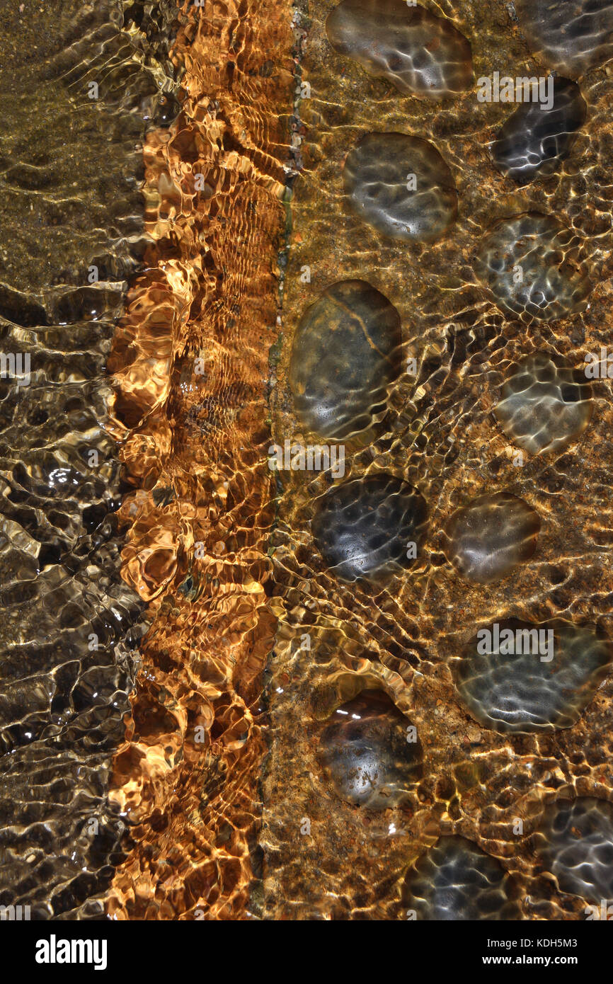 Clear, clean water rippling over black rocks set in  brown concrete, creating golden patterns; feeling of motion - Stock Image