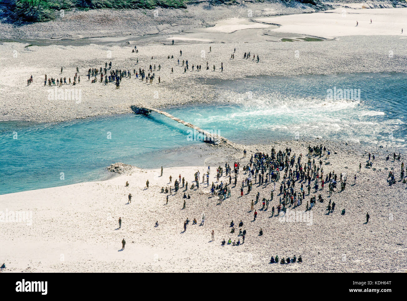 Upper Indus Valley near Skardu, Pakistan, 1990; Villagers gather on either side of a temporary bridge over the River - Stock Image