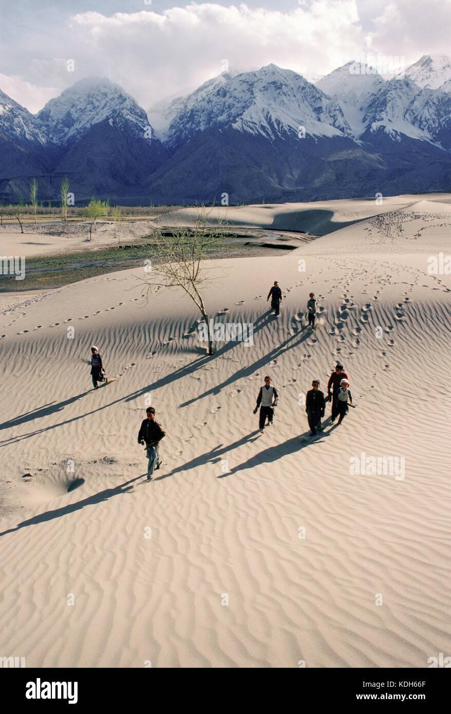 Boys return from school across sand dunes in Skardu, the upper Indus Valley, Kashmir, Pakistan, 1990. - Stock Image