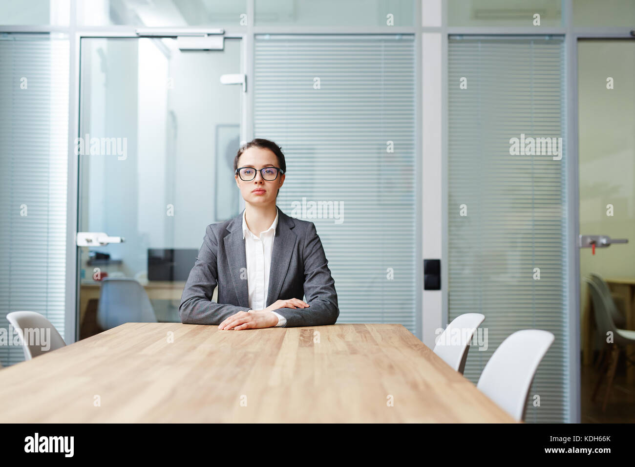 Serious employer waiting for another applicant by table in boardroom - Stock Image
