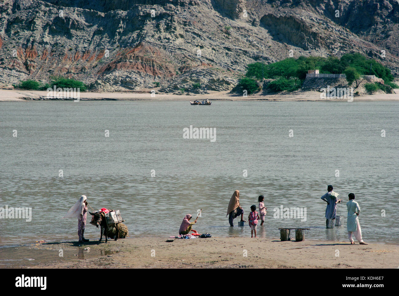 People wash clothes and fetch water on the River Indus at Hund, Khyber Pakhtunkhwa, province, Pakistan. - Stock Image