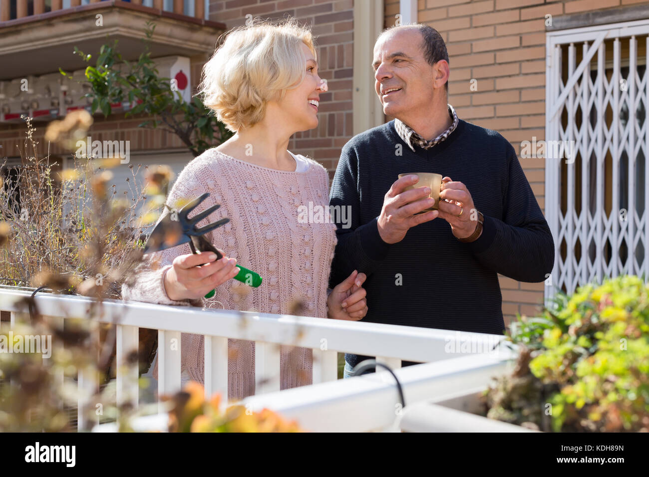 Smiling elderly woman with horticultural sundry and aged man drinking tea in patio Stock Photo