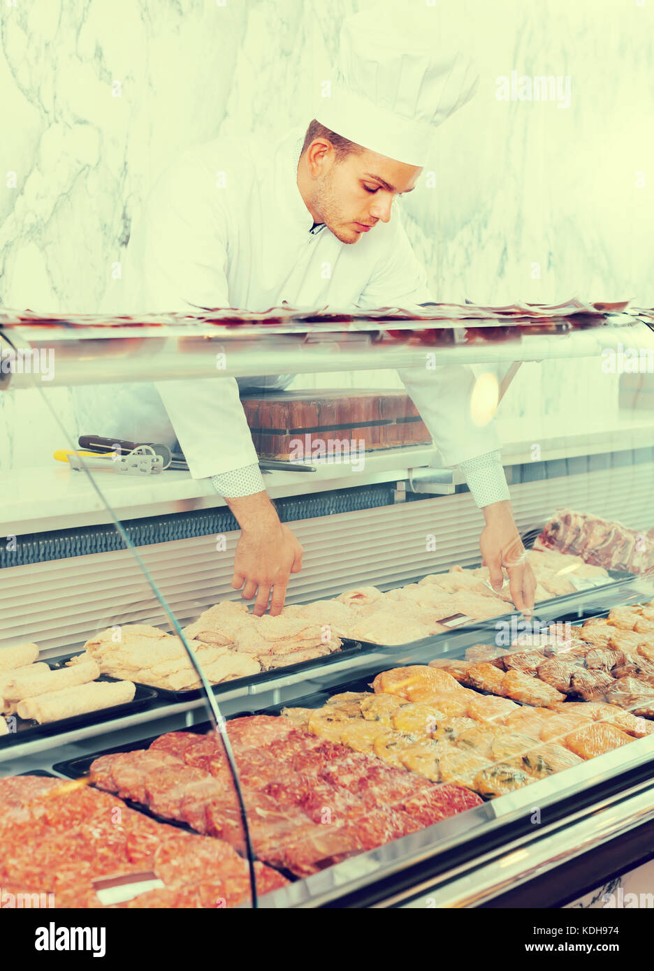 concentrated young seller at butcher store offering fresh products Stock Photo