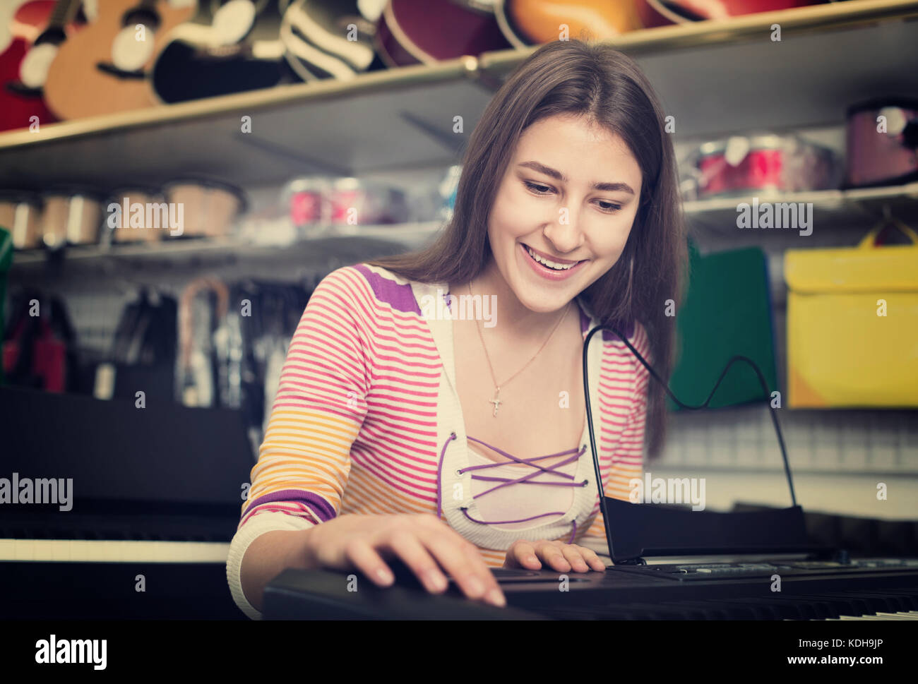 Teenage girl choosing synthesizer in music instruments shop - Stock Image