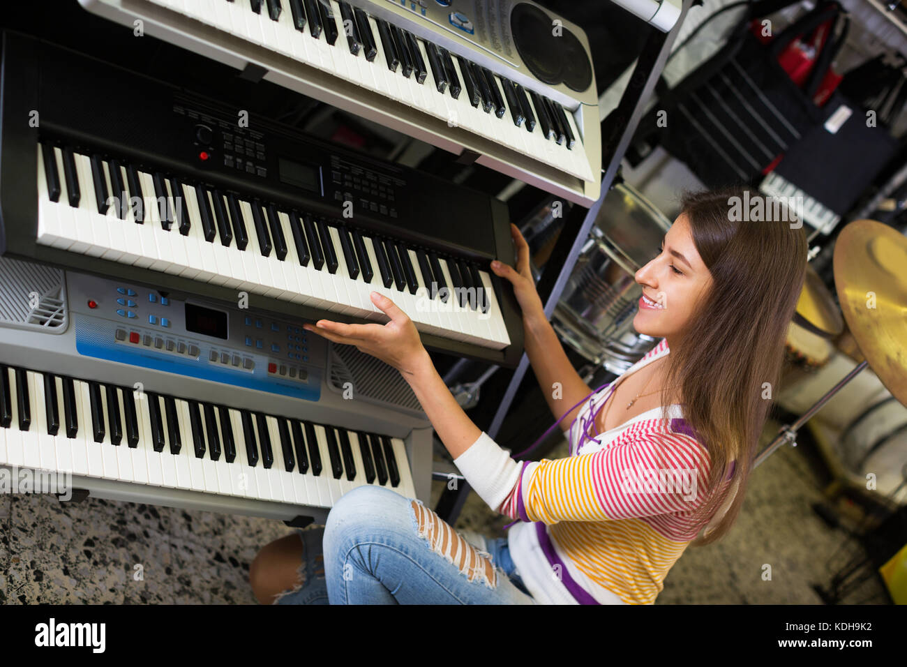 Happy adult girl selecting control keyboard for synthesiser in shop - Stock Image