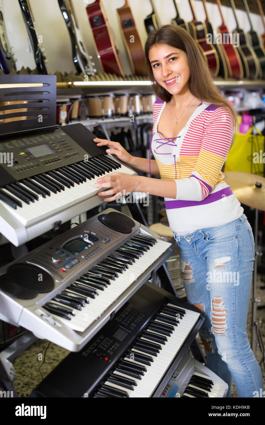 Young female customer choosing synthesizer in store and smiling - Stock Image