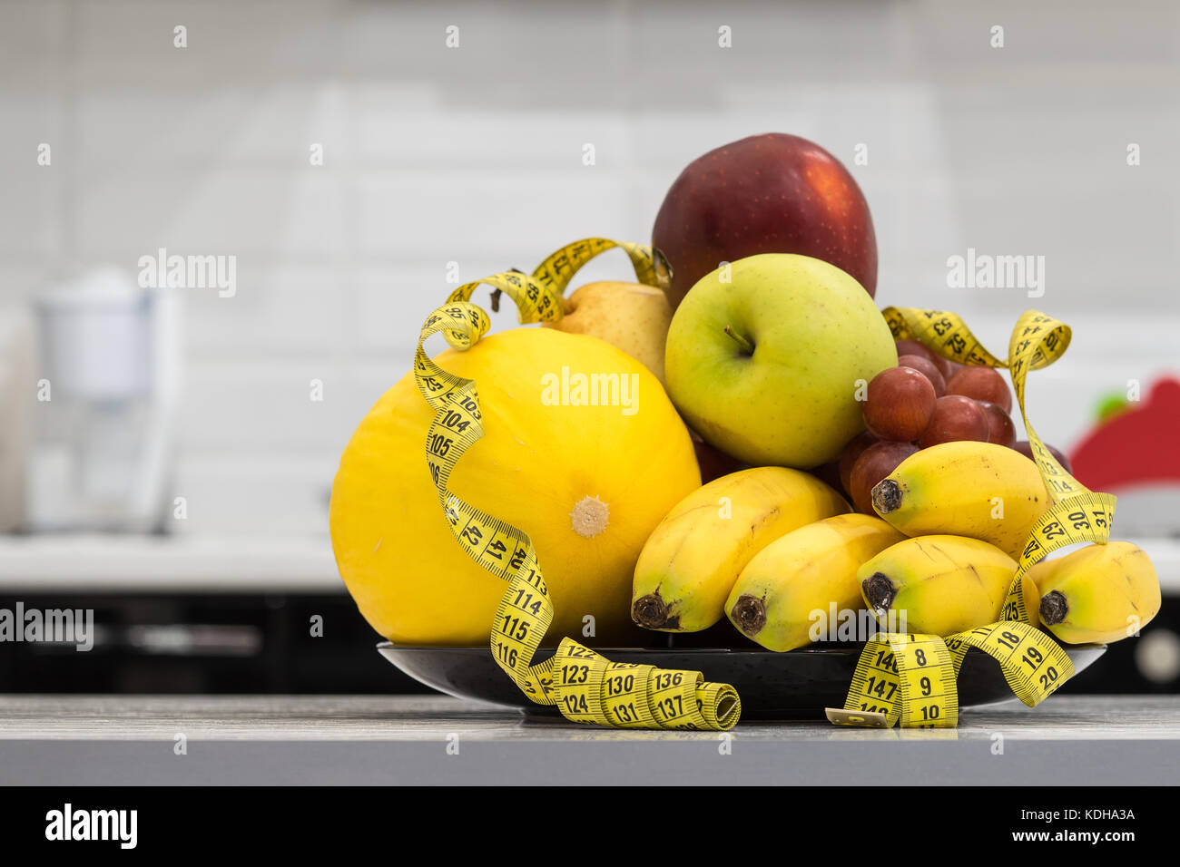 Concept of diet. Low-calorie fruit diet. Diet for weight loss. Plate with measuring tape and fruits on the table. - Stock Image