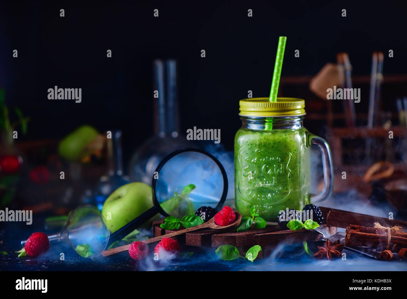 Smoothie jar with green helthy drink in a still life with berries, cinnamon, anise, magnifying glass and nutrition - Stock Image