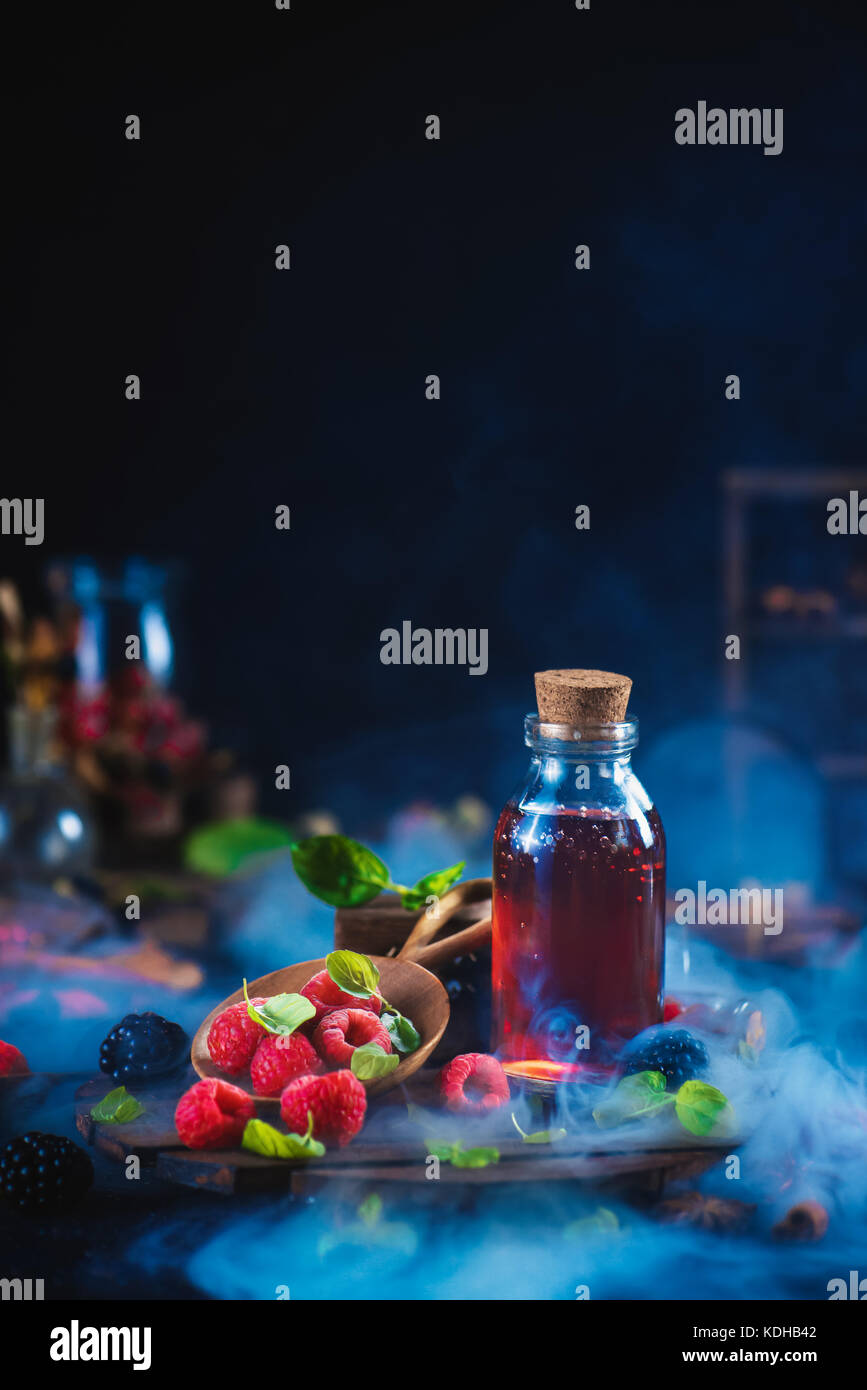 Raspberry potion with a wooden bowl of berries and mint leaves on a dark background. Magical still life with a mystic Stock Photo
