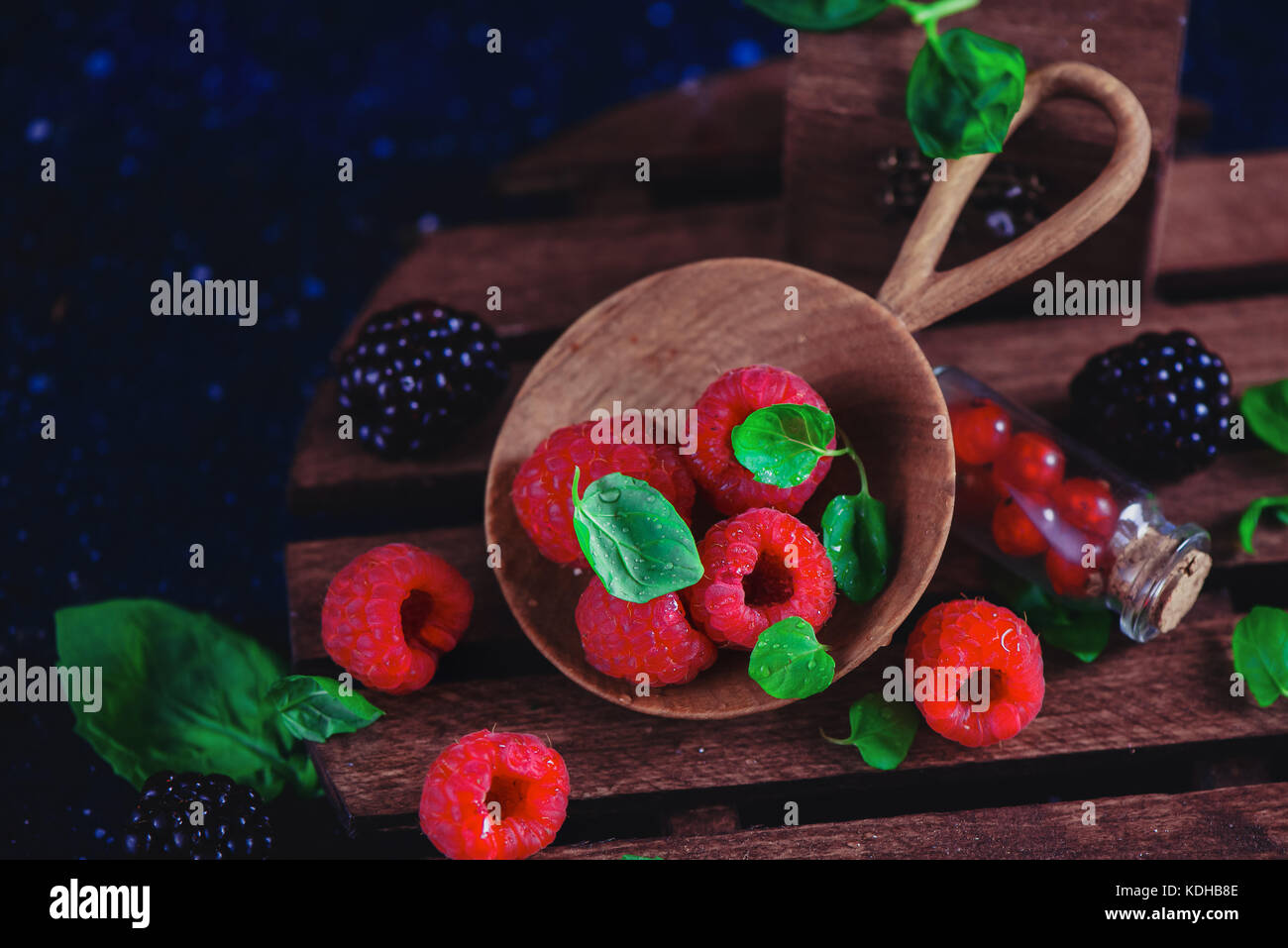 Assorted berries in a handmaiden wooden plate. Raspberry and blackberry with green mint leaves. Dark food photography Stock Photo