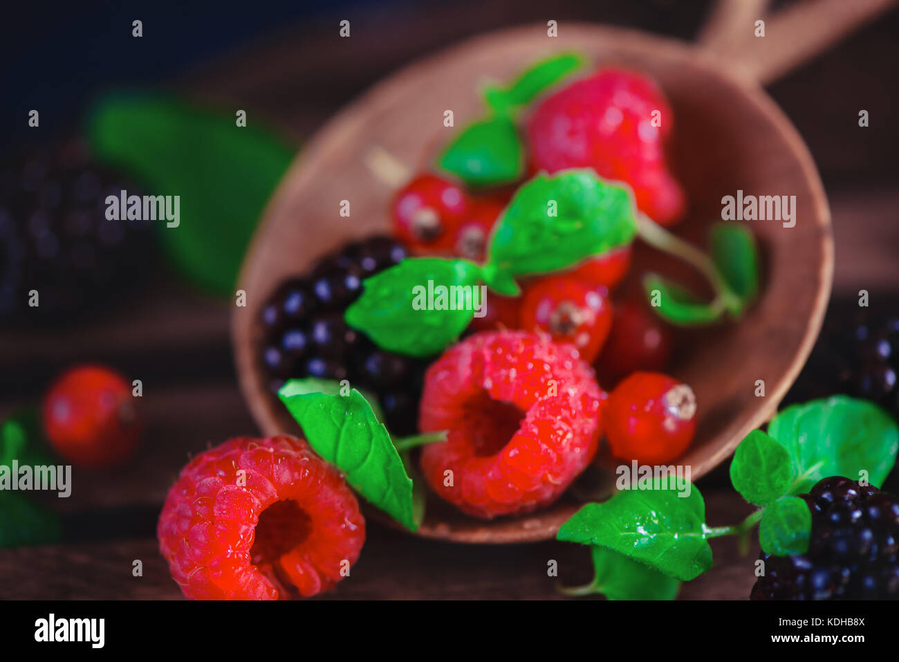 Close-up of tiny wooden bowl with fresh raspberries, blueberries, currant and mint leaves. Dark food photography - Stock Image