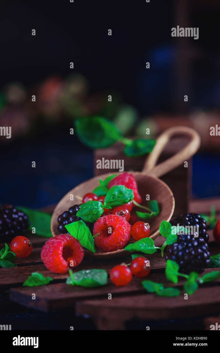 Summer still life with berries in a wide wooden spoon on a dark background. Raspberry and blackberry with green Stock Photo