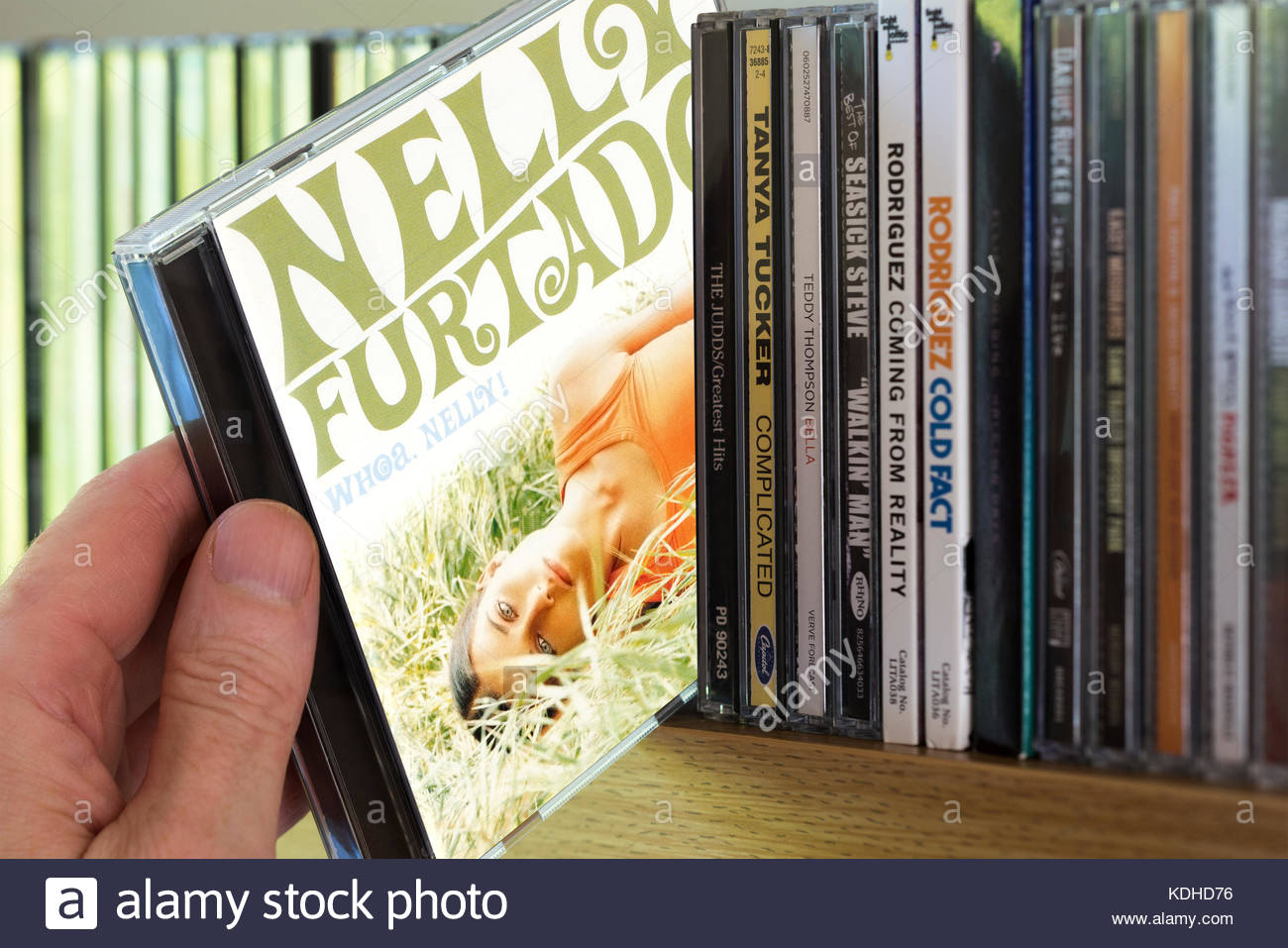 Whoa Nelly , Nelly Furtado CD being chosen from a shelf of other CD's, Dorset, England Stock Photo