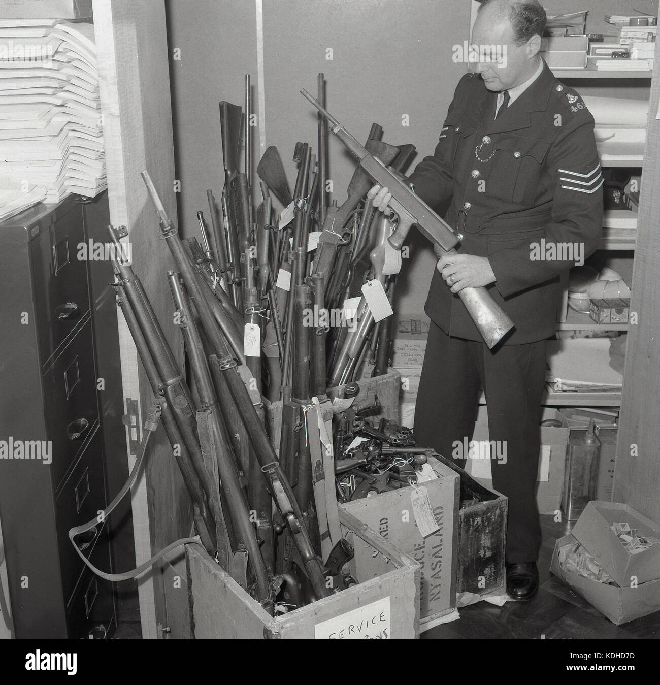 1960s, historical, male British police sergeant holding a rifle, selected from a stash of rifles, handguns and other - Stock Image