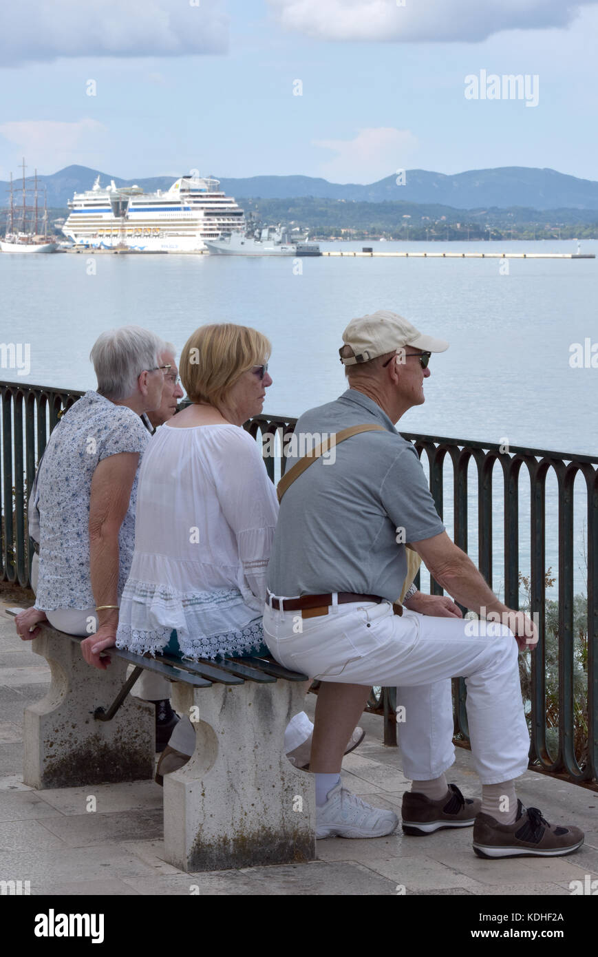 four older or elderly pensioners sitting on a bench in Kerkira, corfu, Greece with a cruise ship or liner in the - Stock Image