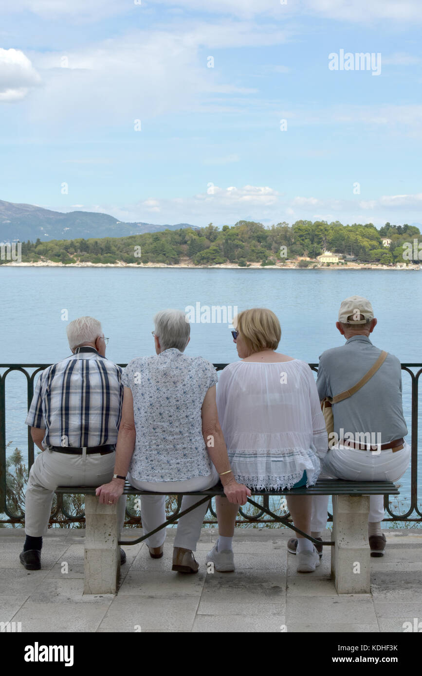 two married couples or four pensioners or elderly people sitting on a bench looking out to sea while on holiday - Stock Image