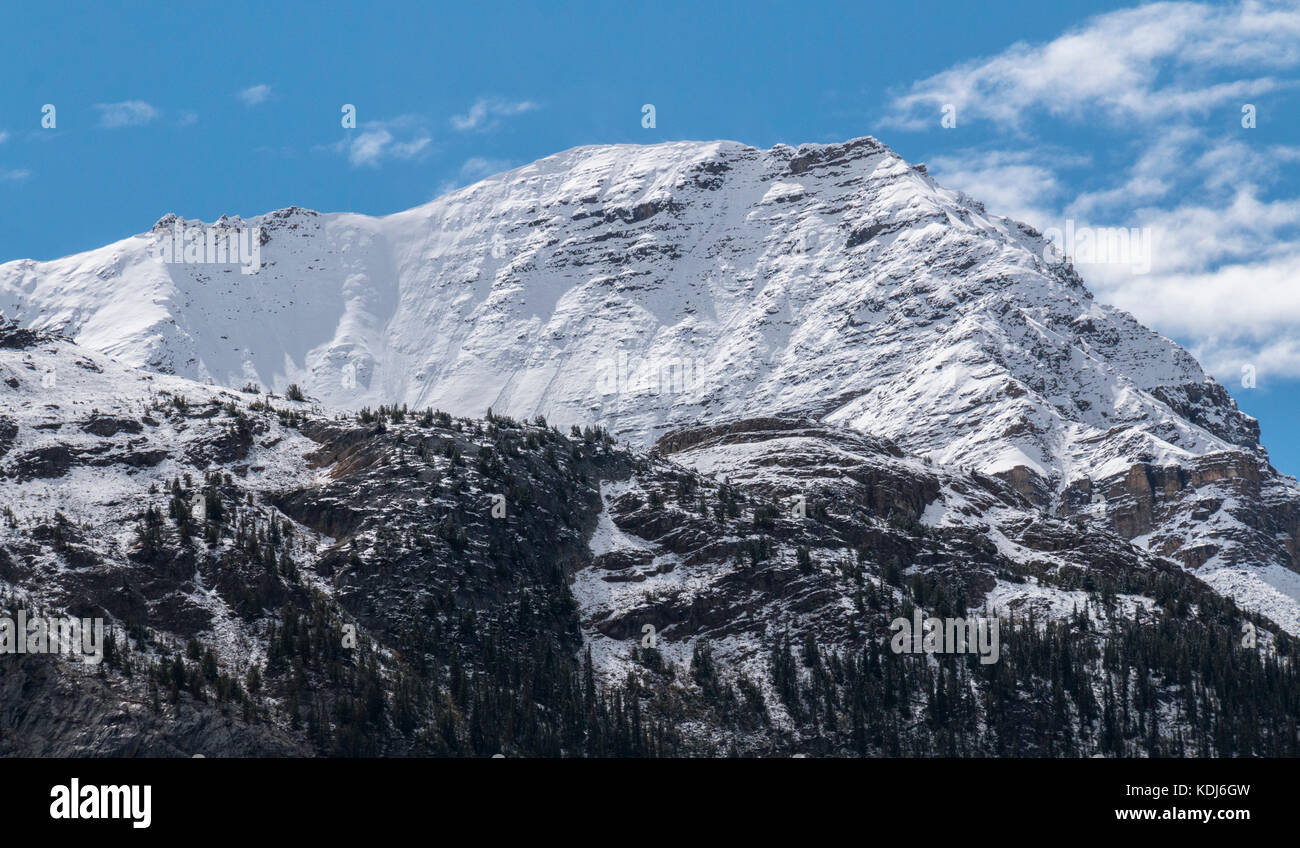 Blue skies over an immense mountain in Jasper National Park in Alberta, Canada. - Stock Image