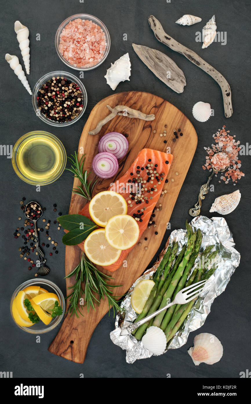 Healthy heart food with fresh salmon, seasoning, fruit, vegetables and olive oil on a wooden board on slate background. - Stock Image