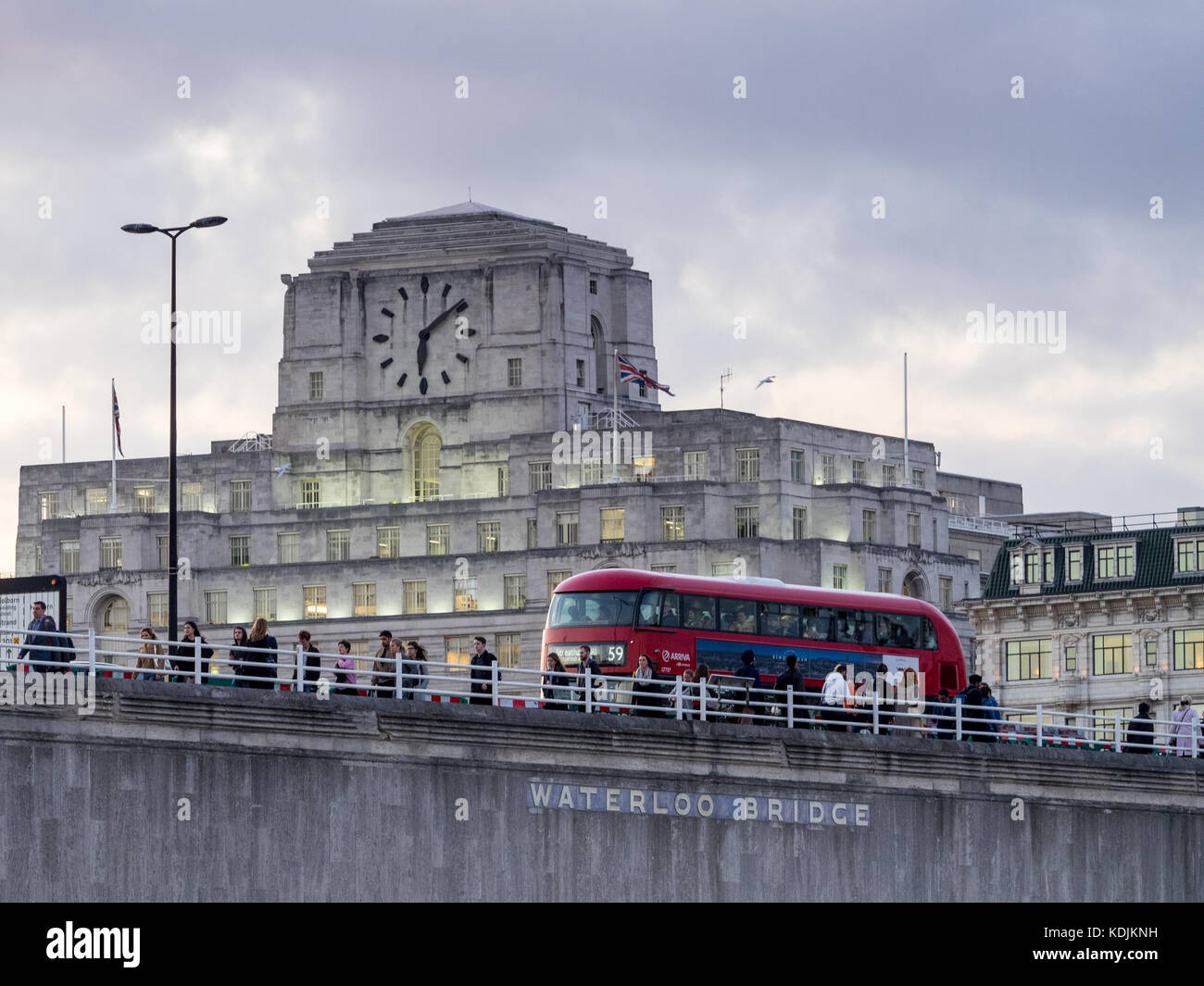 London Bus and commuters cross Waterloo Bridge in front of Shell Mex House in central London at dusk Stock Photo