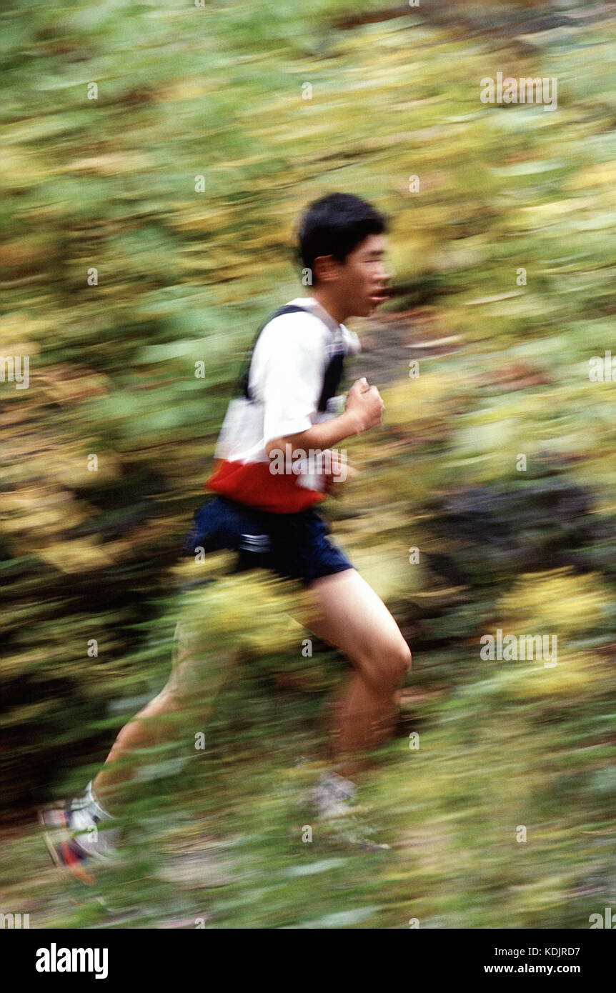 Blurred action of High School boys cross country running race. - Stock Image
