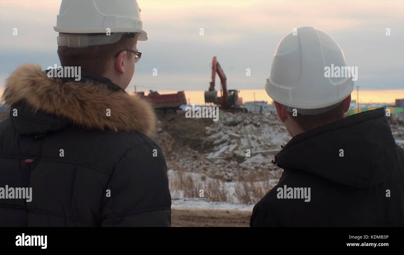 Back view of architects inspecting construction site. Two engineers in hard hats on construction site excavator - Stock Image