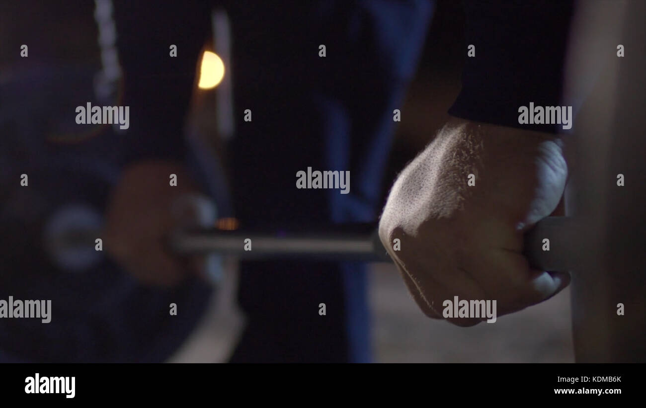 Grip - barbell bench press. Man grips bar for barbell bench press. Macro. Focus on hand. The guy doing bench press - Stock Image