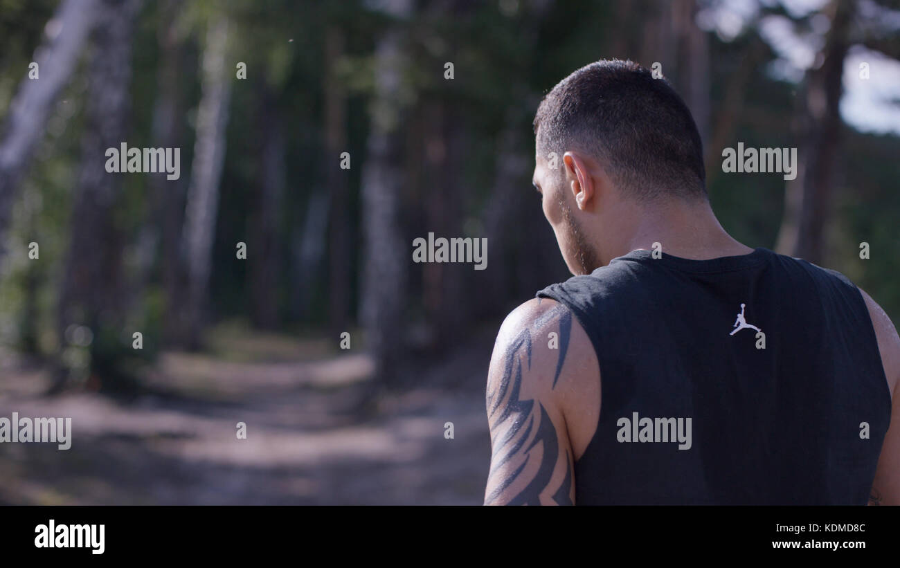 Athletic man after run. Handsome man resting after jog at the park on a sunny day. Sweaty sportsman in park - Stock Image