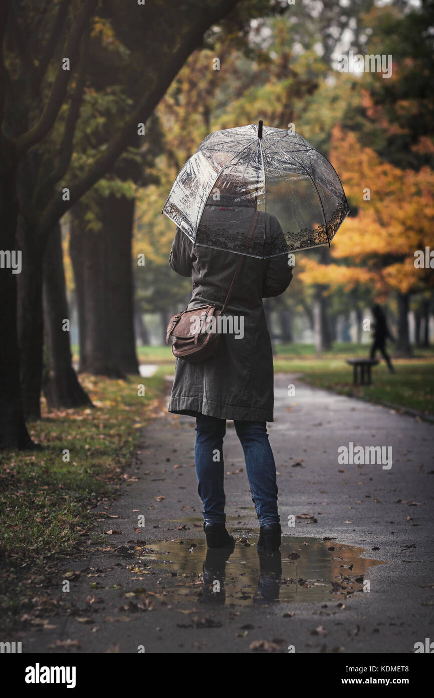 Woman with transparent umbrella on a rainy day standing in a puddle - Stock Image