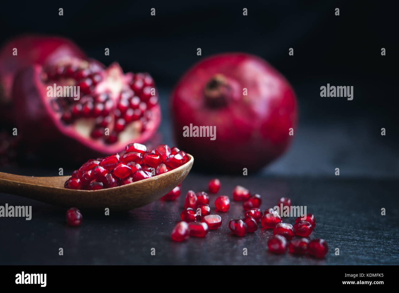 fresh juicy pomegranate diet fruit is a natural antioxidant on black background - Stock Image