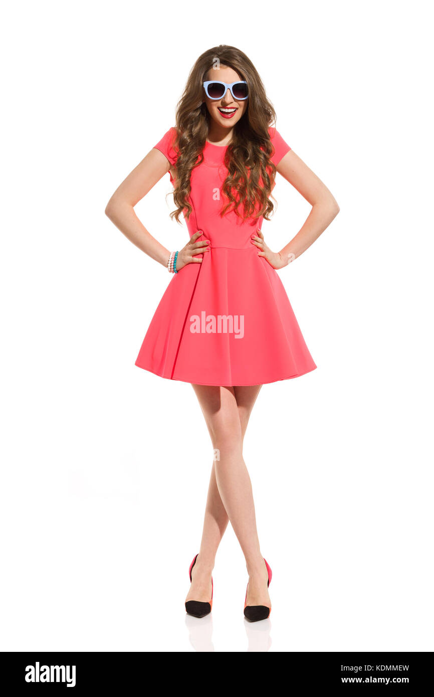 Beautiful young woman in pink mini dress, blue sunglasses and high heels is standing with legs crossed and laughing. - Stock Image