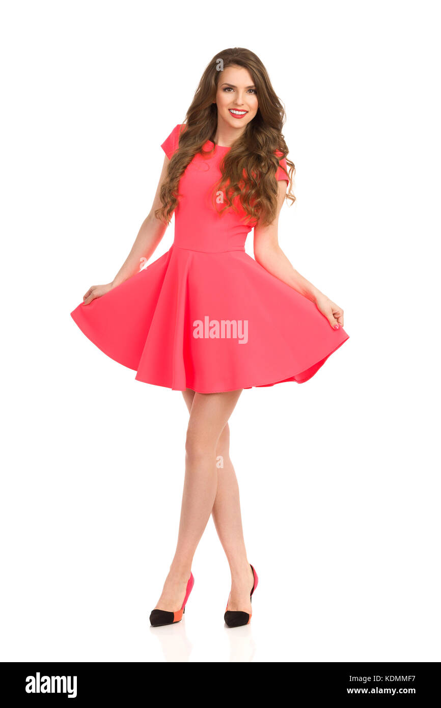Beautiful young woman in pink mini dress and high heels is standing with legs crossed and smiling. Full length studio - Stock Image