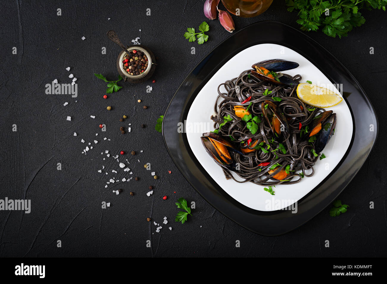 Black spaghetti. Black seafood pasta with mussels over black background. Mediterranean delicacy food. Flat lay. - Stock Image