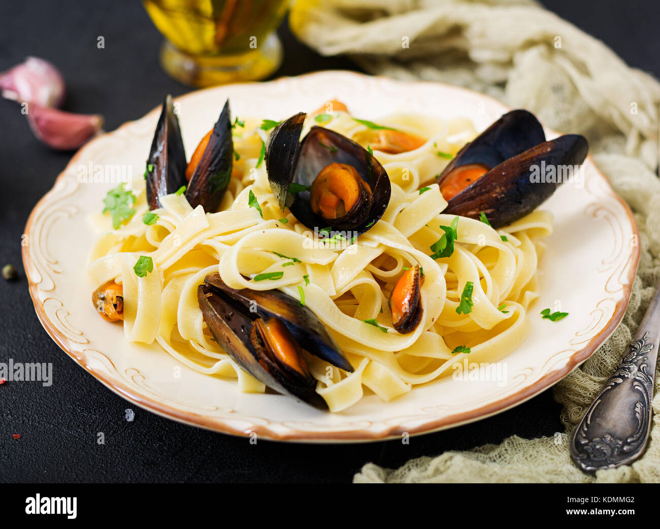 Seafood fettuccine pasta with mussels over black background. Mediterranean delicacy food. - Stock Image