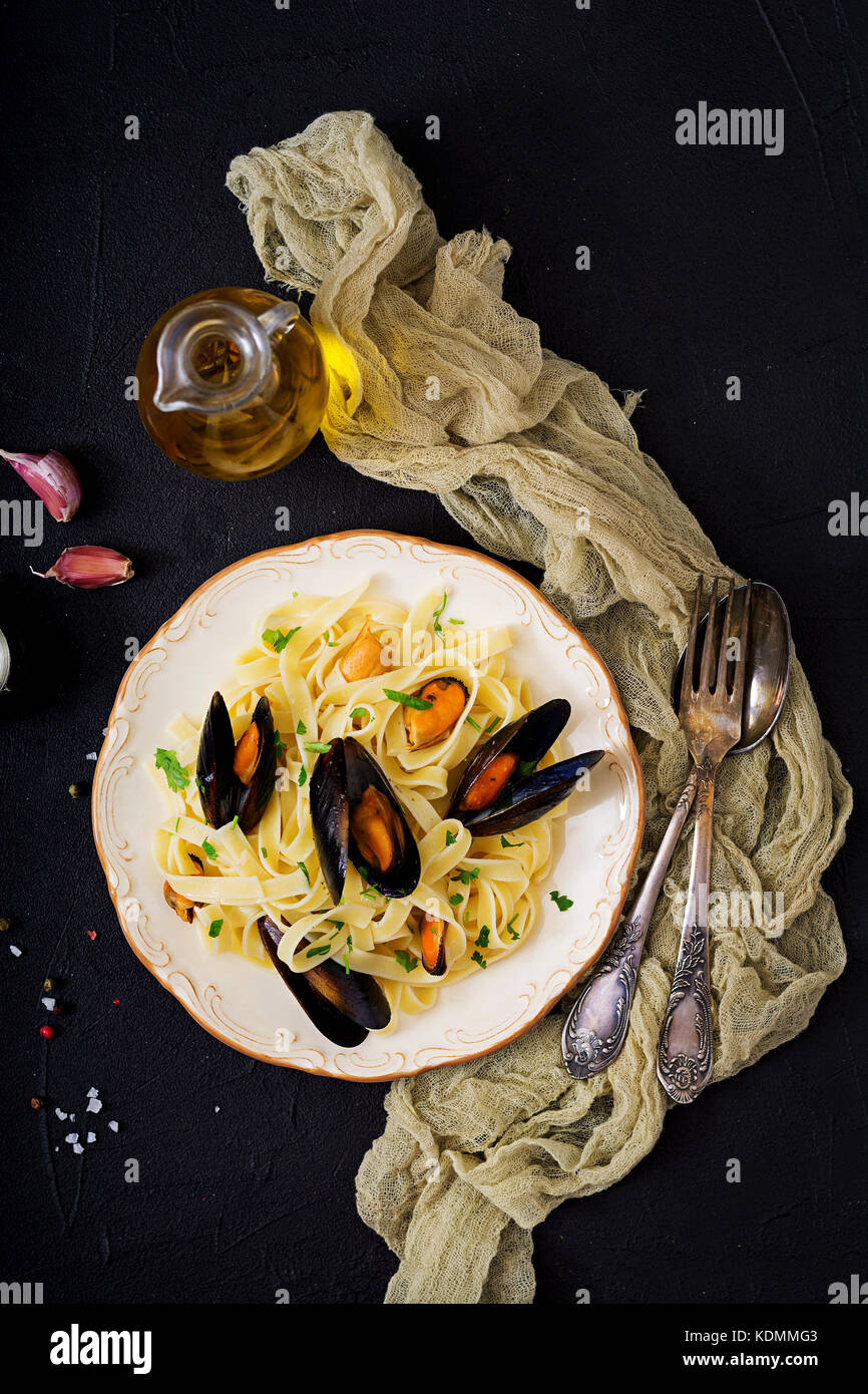 Seafood fettuccine pasta with mussels over black background. Mediterranean delicacy food. Flat lay. Top view - Stock Image