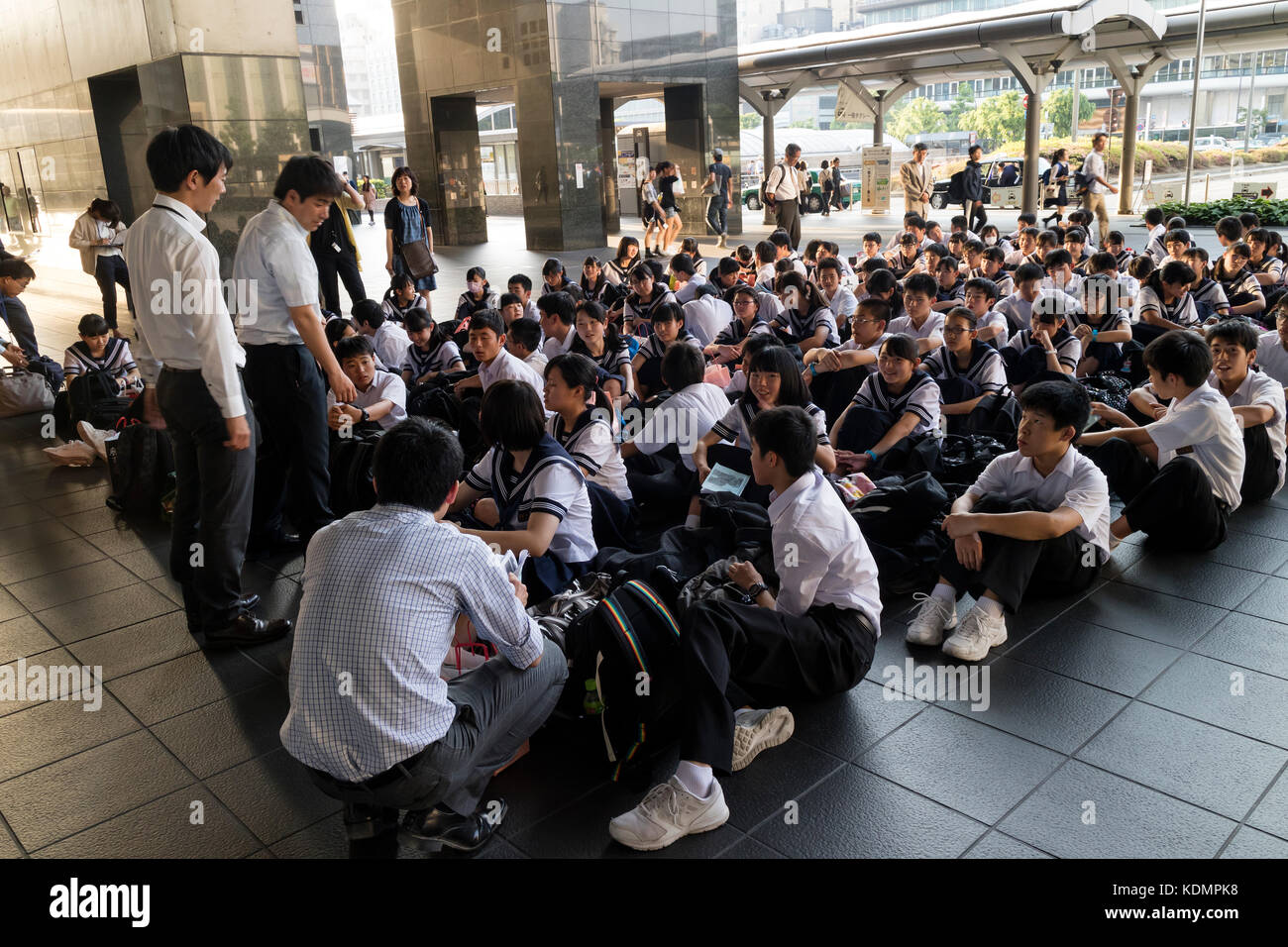 Kyoto, Japan - May 21, 2017: Class of schoolchildren in uniform waiting in the Kyoto station - Stock Image
