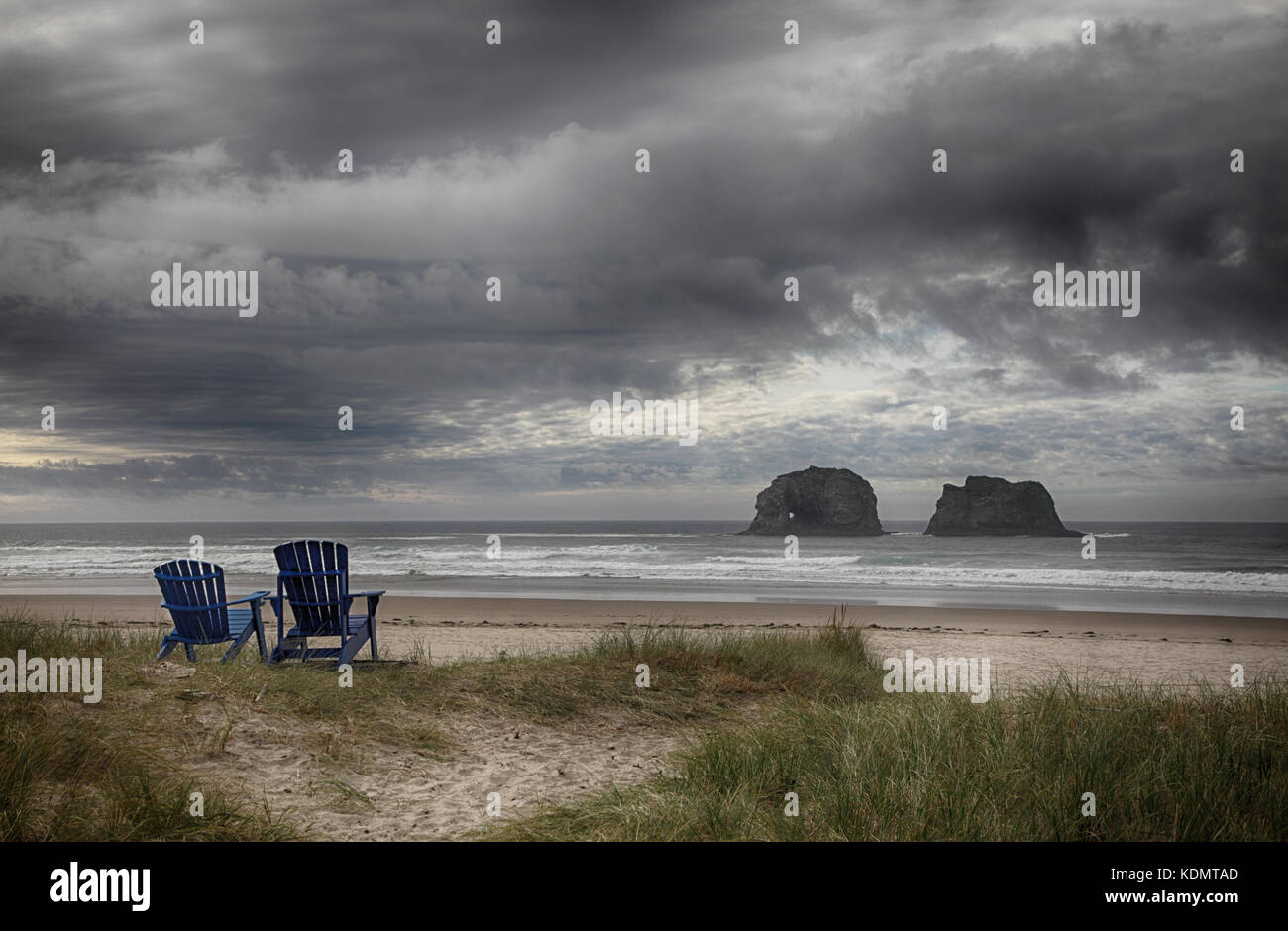 A romantic oceanscape with moody sky including two Adirondack chairs facing out to sea stack rock formations in - Stock Image
