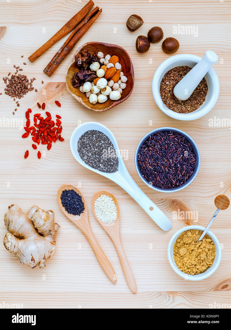 Nutritious Foods and Super foods selection with supplement powders in mortar and spoons setup on wooden background. - Stock Image