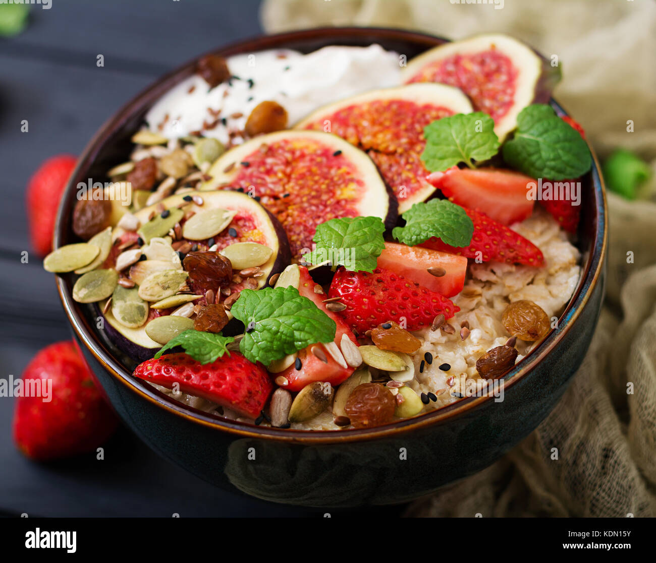 Delicious and healthy oatmeal with figs, seeds, strawberry and yogurt. Healthy breakfast. Fitness food. Proper nutrition. - Stock Image