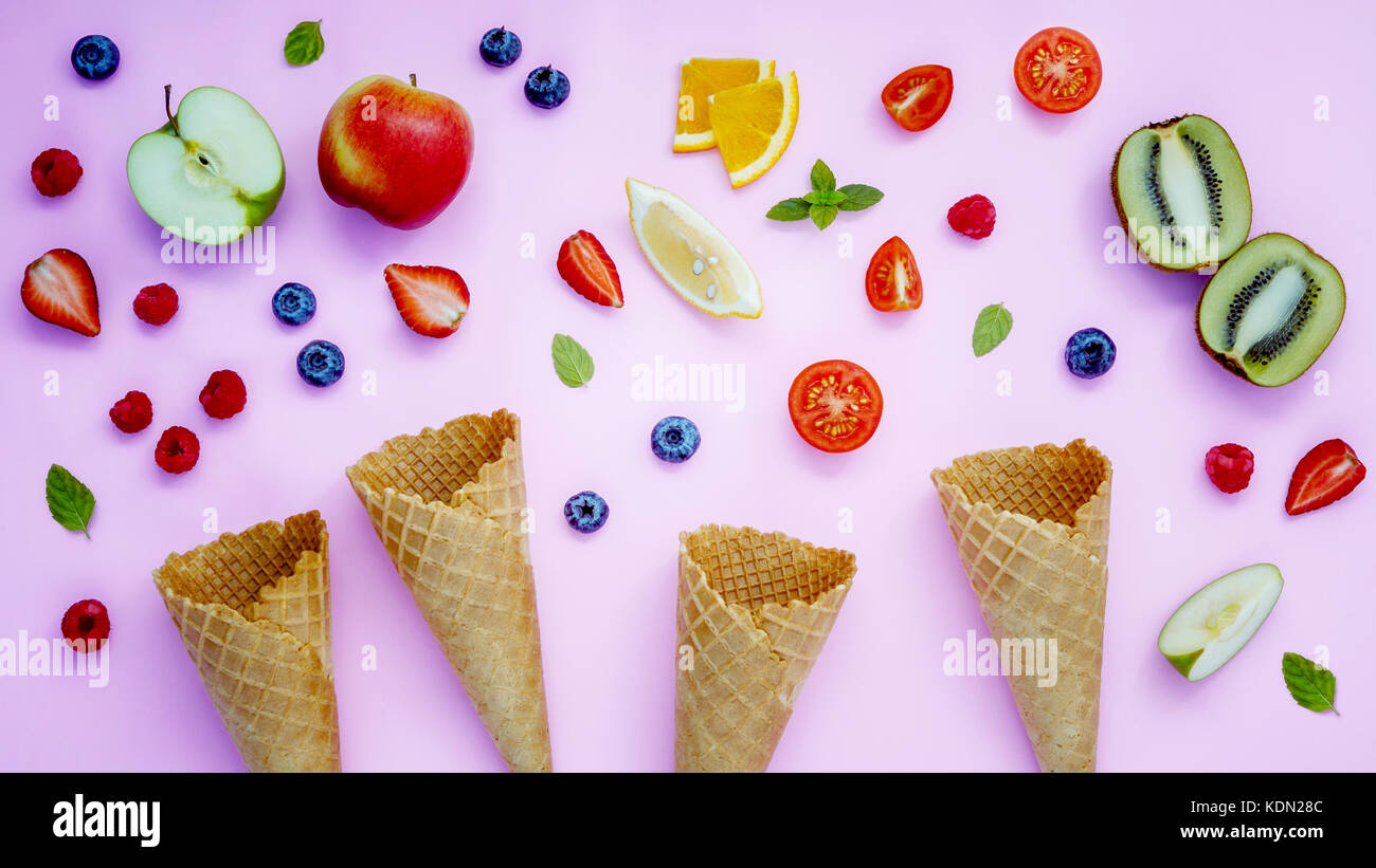 Cones and colorful various fruits raspberry ,blueberry ,strawberry ,orange slice , half kiwi ,apple,tomato and peppermint - Stock Image