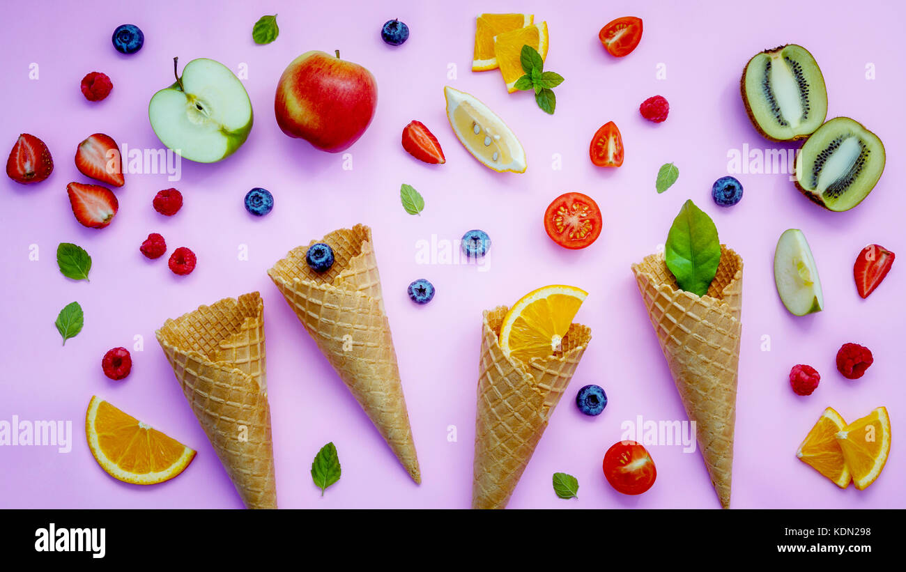 Cones and colorful various fruits raspberry ,blueberry ,strawberry ,orange slice , half kiwi ,apple,tomato and peppermint Stock Photo
