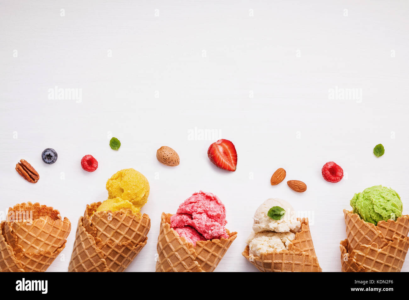 Colorful ice cream with cones and various fruits raspberry ,blueberry ,strawberry ,almonds and peppermint leaves Stock Photo