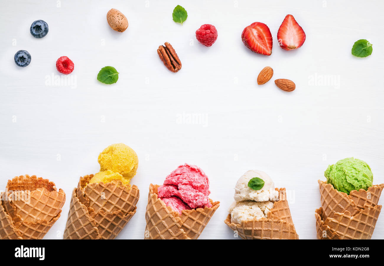 Colorful ice cream with cones and various fruits raspberry ,blueberry ,strawberry  and peppermint leaves setup on - Stock Image
