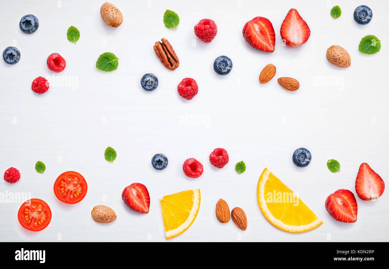 Colorful various fruits raspberry ,blueberry ,strawberry ,orange slice ,pecan ,almonds ,tomato and peppermint leaves - Stock Image