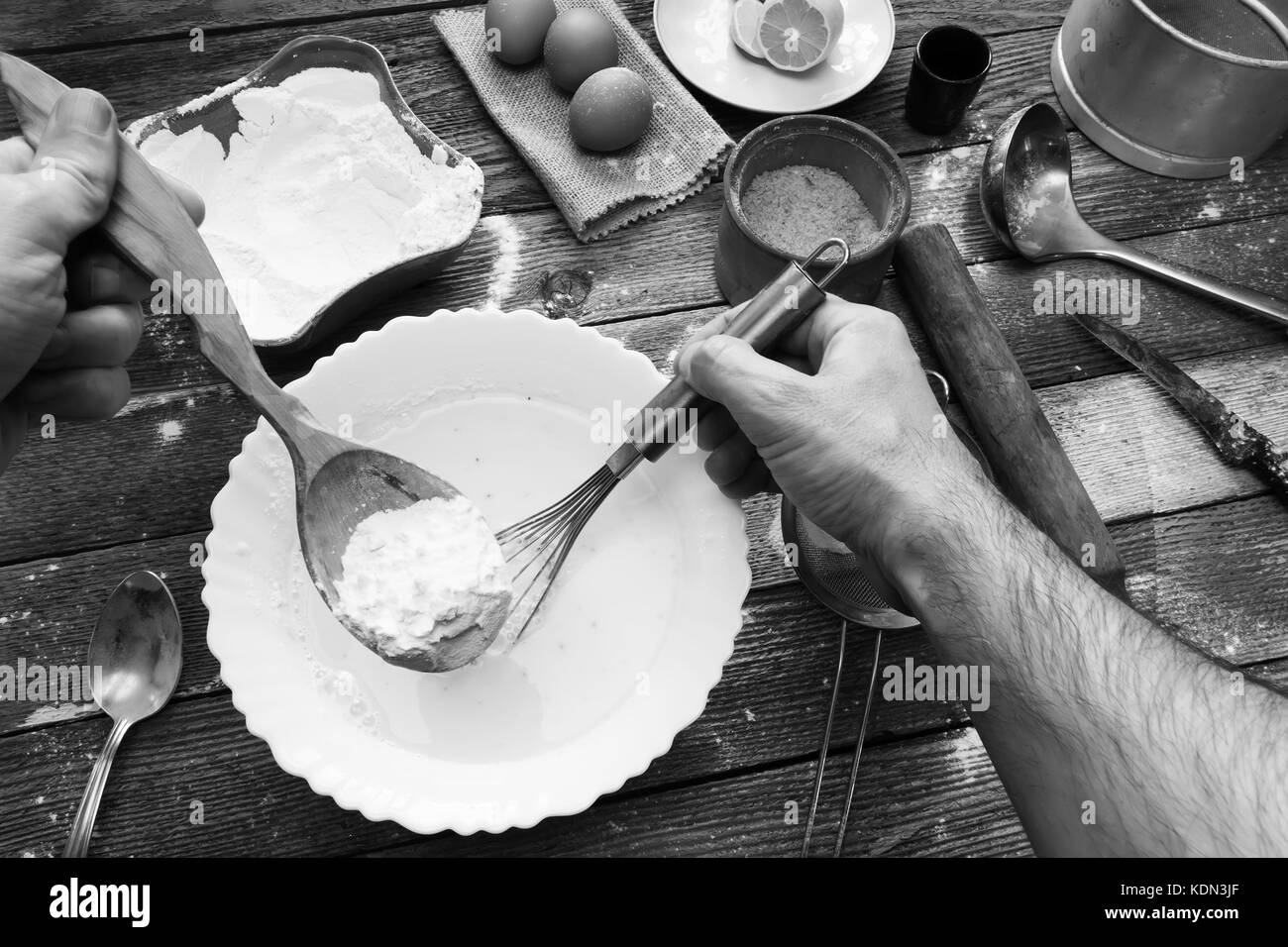 The man knead the dough with a whisk. Wheat flour, batter, eggs, a lemon and kitchen utensils on wooden table. Preparation - Stock Image