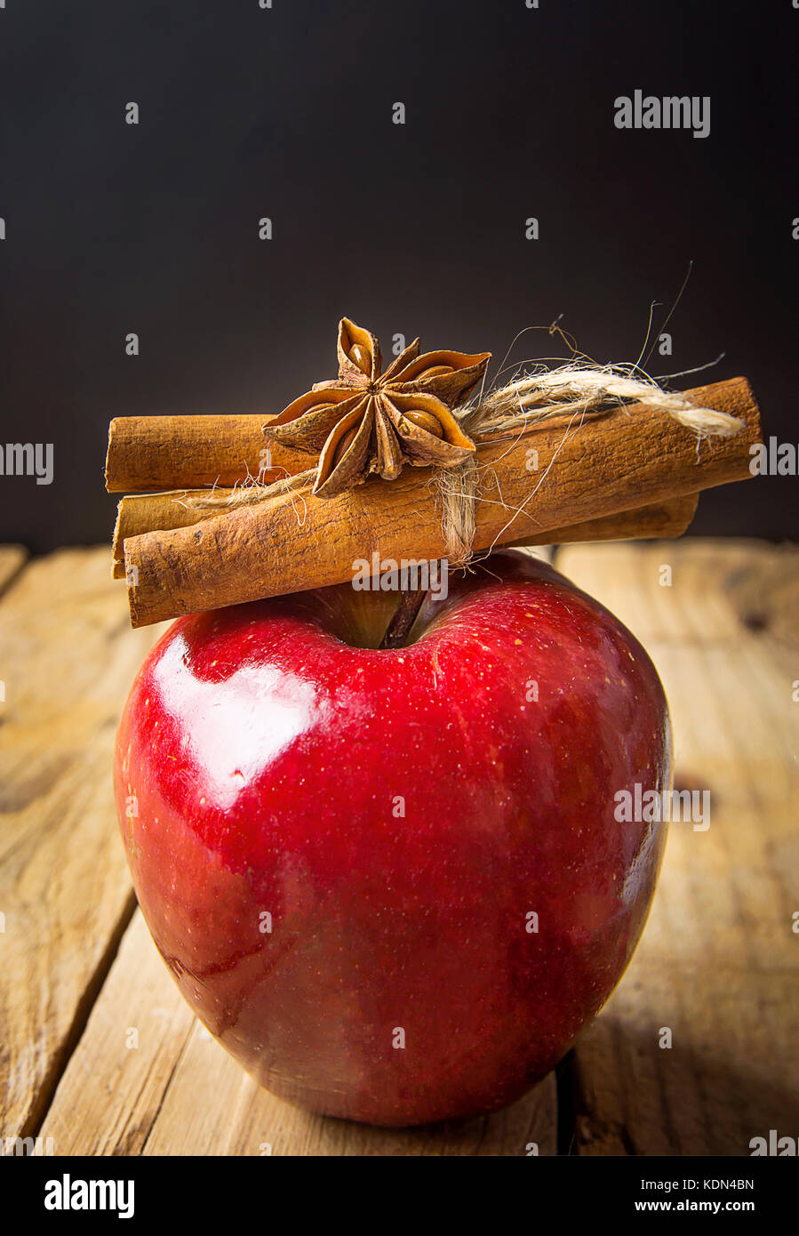 Red Glossy Apple Cinnamon Sticks Tied with Twine Anise Star on Wood Background. Vintage Rustic Style. Christmas - Stock Image